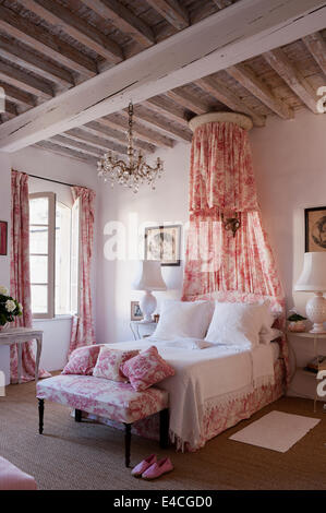 Pink and white toile de jouy fabric on cushions, curtain and bed coronet canopy in bedroom with wooden ceiling beams - Stock Photo