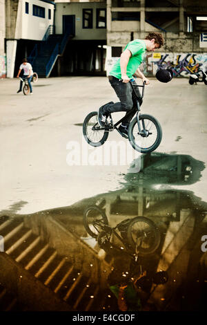 BMX biker performing a stunt over a puddle, man in background - Stock Photo