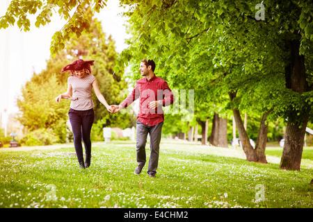 Happy young couple in park holding hands, Osijek, Croatia - Stock Photo