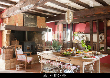 Large rustic French country kitchen with old ceiling beams, woodburning stove and laid table - Stock Photo
