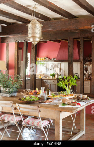 Laid table in large rustic French country kitchen with old ceiling beams - Stock Photo