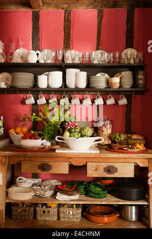 Open shelving in rustic French country kitchen with timber framed walls and rendered infill - Stock Photo