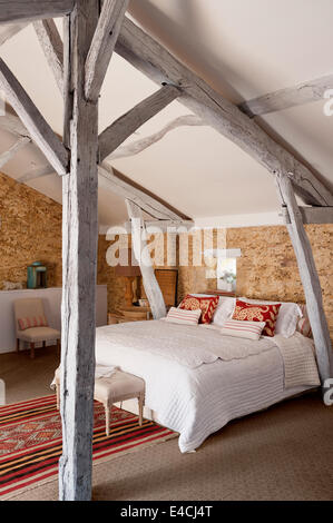 Attic Bedroom With Exposed Beams And Wooden Floorboards