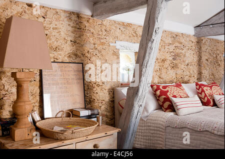 Wooden lampstand on bedside table in bedroom with exposed stone walls and wooden ceiling beams - Stock Photo