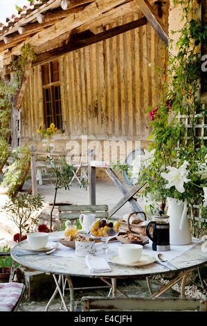 Breakfast laid on round table with folding bistro chairs in courtyard by old barn