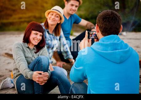 Man taking pictures of friends outdoors, Osijek, Croatia - Stock Photo