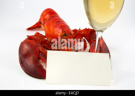 Whole cooked lobster holding a  glass of white wine and a recipe or menu card - Stock Photo