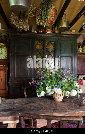 Vase of flowers on narrow wooden table in country kitchen with old cabinet - Stock Photo