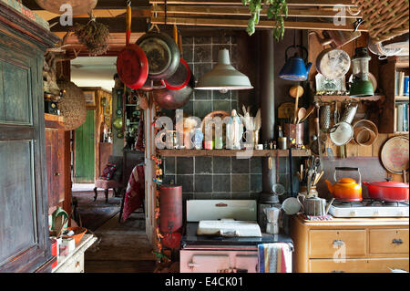 Rayburn Regent stove in cluttered country kitchen with pans hung from the ceiling - Stock Photo