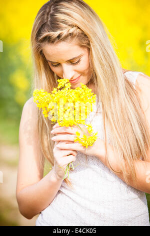 Young woman smelling colza flowers, Tuscany, Italy - Stock Photo