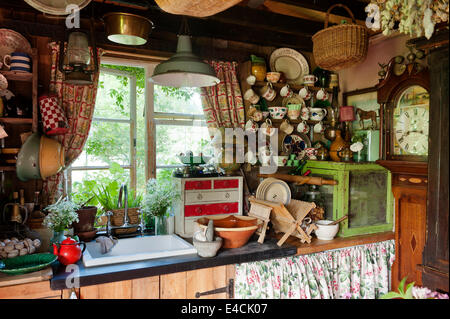 Sink area in shabby chic country kitchen with china adorning every surface and a grandfather clock in the corner - Stock Photo