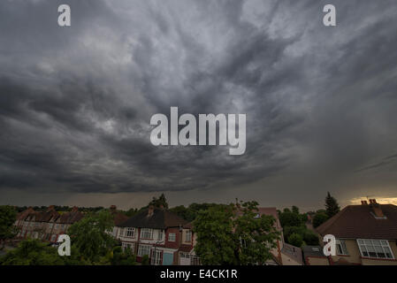 Wimbledon, London, UK. 8th July, 2014. A large mass of rain cloud passes over the south London suburb at dusk after - Stock Photo