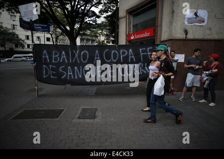 Belo Horizonte, Brazil. 8th July, 2014. Residents pass by a slogan protesting against the organization of the FIFA - Stock Photo