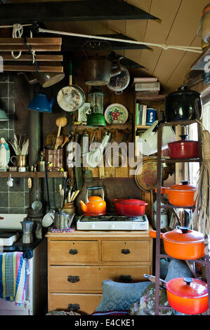 Le creuset pots on an iron rack in cluttered country kitchen with gas stove - Stock Photo