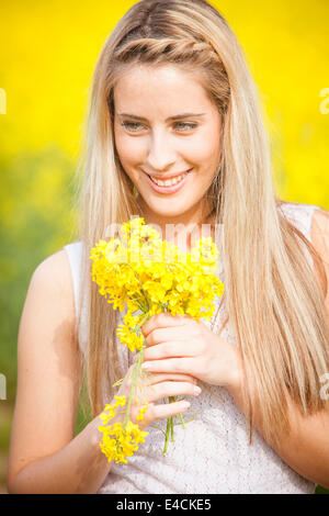 Blonde woman holding bunch of colza flowers, Tuscany, Italy - Stock Photo