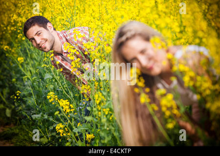 Young couple in colza field playing hide and seek, Tuscany, Italy - Stock Photo