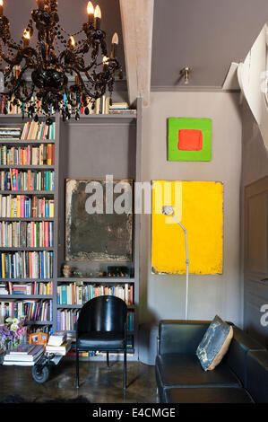 Black leather Corbusier sofa in sitting room with bookshelving, chrome candelabra and black chair both from Le Pigeon - Stock Photo