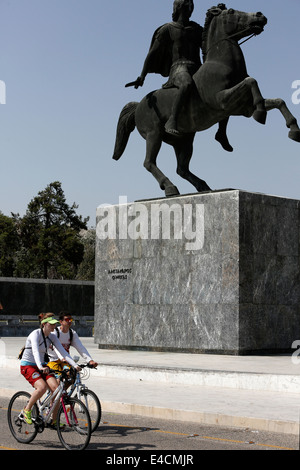 A couple bicycling in front of Alexander the Great statue in Thessaloniki, Greece - Stock Photo