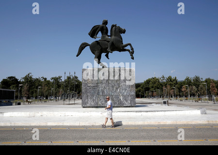 A man walks in front of Alexander the Great statue in Thessaloniki, Greece - Stock Photo