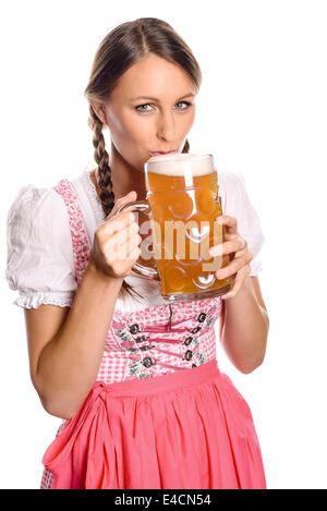 Attractive young woman with her hair in plaits wearing a dirndl drinking beer from a very large glass tankard with - Stock Photo