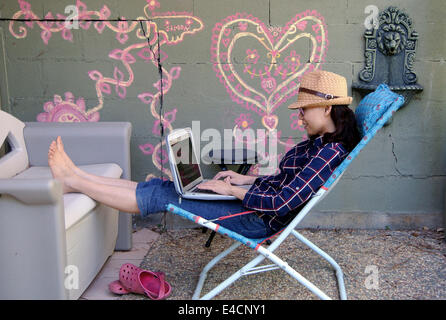 barefoot woman in straw hat  relaxes on patio in lawn chair  with laptop - Stock Photo