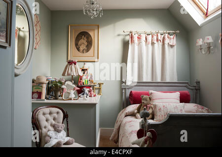 Isobella fabric by Kate Forman on small antique bed in childs bedroom with buttoned chair and assorted toys - Stock Photo