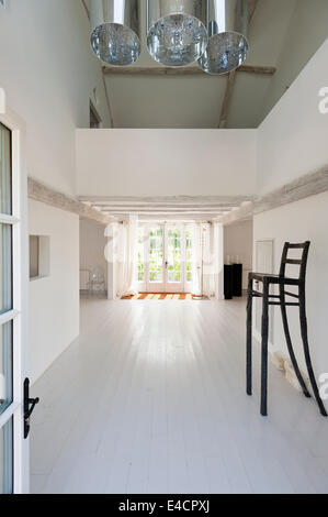 Tall iron chair in open plan minimalist white hallway with wooden flooring and ceiling beams - Stock Photo