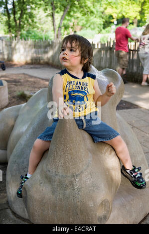 Three Year Old Boy Sitting on Rhinoceros Scupture at the Louisville Zoo in Kentucky - Stock Photo