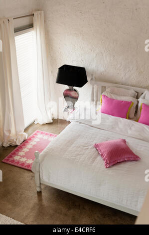 Pink cushions on white bed in bedroom with pink carpet - Stock Photo