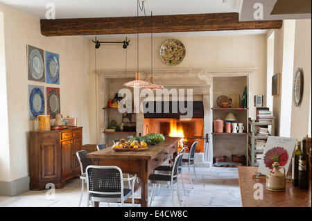 Provencal kitchen with large stone fireplace and wooden dining table. The copper pendant lights are an Arne Jacobsen - Stock Photo