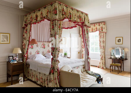 Fourposter bed with chintz curtains in bedroom with chaise. A Romney drawing hangs above the dressing table - Stock Photo