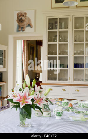 A vase of stargazer lilies adorn a breakfast table laid with Dragon Green crockery by Coalport. - Stock Photo