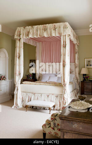 Fourposter bed with chintz curtains in olive green bedroom. Paint by Farrow and Ball - Stock Photo
