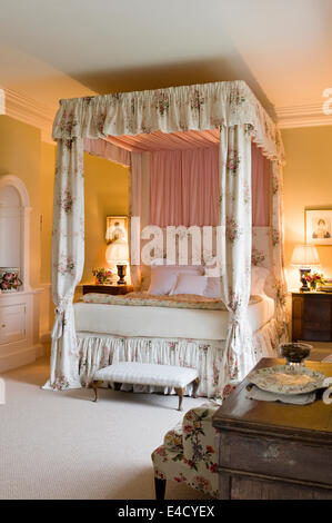 Four poster bed with chintz curtains in olive green bedroom. Paint by Farrow and Ball - Stock Photo