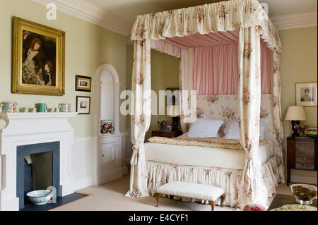 Fourposter bed with chintz curtains in olive green bedroom with fireplace. Paint by Farrow and Ball - Stock Photo