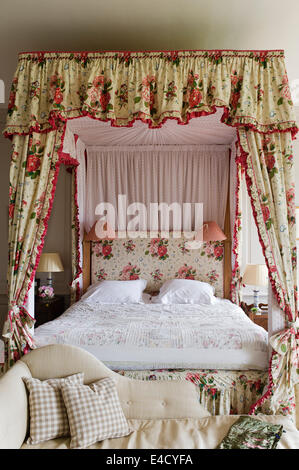 A chaise at the foot of a four poster bed with chintz curtains - Stock Photo