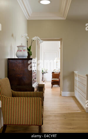 Large wooden chest on landing flanked by a pair of striped armchairs - Stock Photo
