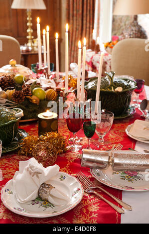 Table laid for christmas dinner with candles and decorations. The tableware is a mix of Luneville Old Strasbourg - Stock Photo