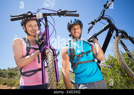 Fit couple walking down trail smiling at camera holding mountain bikes - Stock Photo
