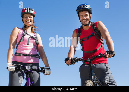 Fit cyclist couple standing at the summit smiling at camera - Stock Photo