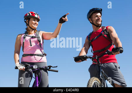 Fit cyclist couple standing at the summit - Stock Photo