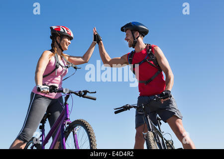 Fit cyclist couple standing at the summit high fiving - Stock Photo
