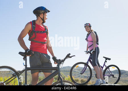 Fit cyclist couple standing at the summit smiling at each other - Stock Photo