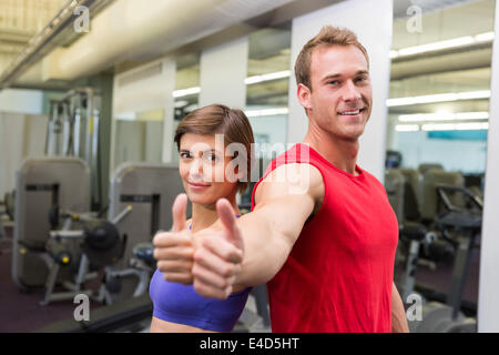 Fit attractive couple smiling at camera showing thumbs up - Stock Photo