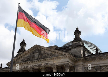 A German flag flies outside of the Bundestag in Berlin, Germany. - Stock Photo