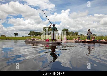 tourists  on a traditional mokoro boat in the Okavango Delta, Botswana, Africa - Stock Photo