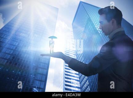 Composite image of businessman holding business man holding umbrella - Stock Photo
