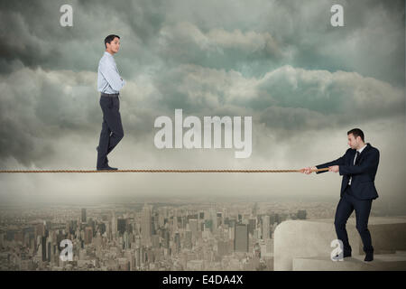 Young business man pulling a tightrope for businessman - Stock Photo