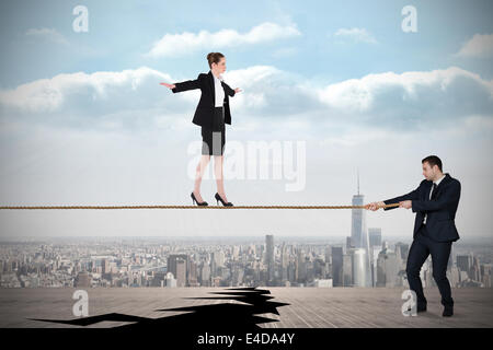 Young business man pulling a tightrope for businesswoman - Stock Photo