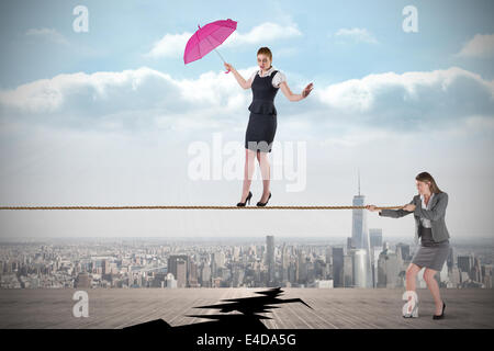 Young business woman pulling a tightrope for businesswoman - Stock Photo